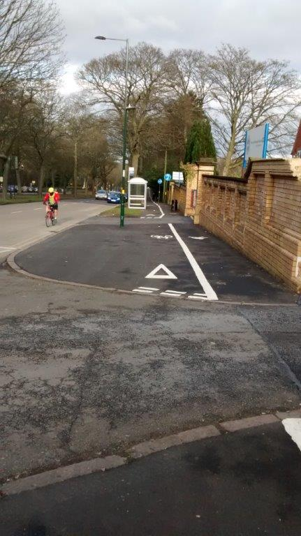 Giveway lines on a cycle lane on the pavement.