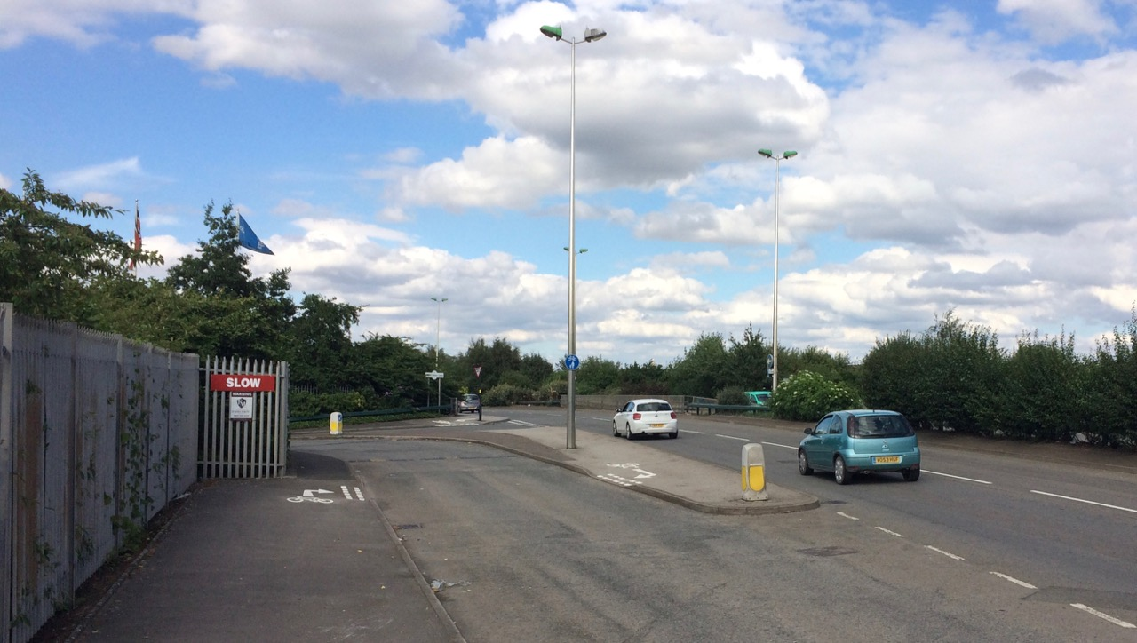 Cycle route crossing entrance to industrial site.
