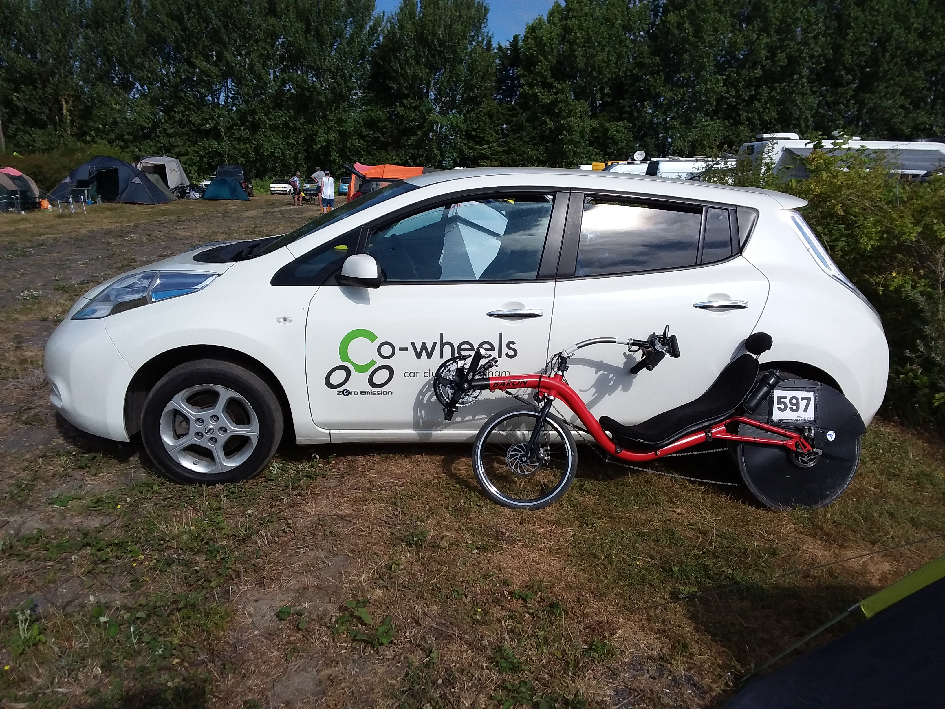 Optima Baron recumbent bicycle with race number 597 leaning against a white Nissan Leaf with a Co-Wheels Birmingham logo on the door panel