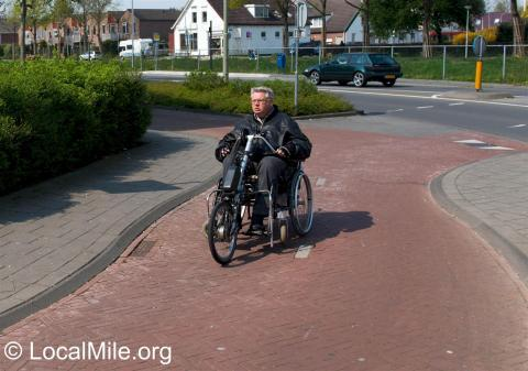 Hand cycle attachment in use on a wheelchair in the Netherlands