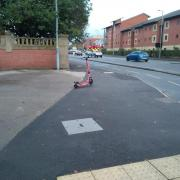 A Voi scooter parked in the middle of a large area of pavement