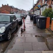 A Voi scooter parked on the pavement, narrowing the gap between a parked car and some bins