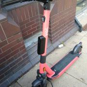 Voi electric hire scooter parked against a wall
