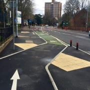 A segregated cycle lane on Wilmslow Road crossing the mouth of a side road