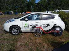 Optima Baron recumbent bicycle leaning against a white Nissan Leaf with a Co-Wheels Birmingham logo