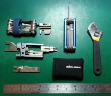 A selection of bicycle multitools, along with an adjustable spanner and a ruler for scale.